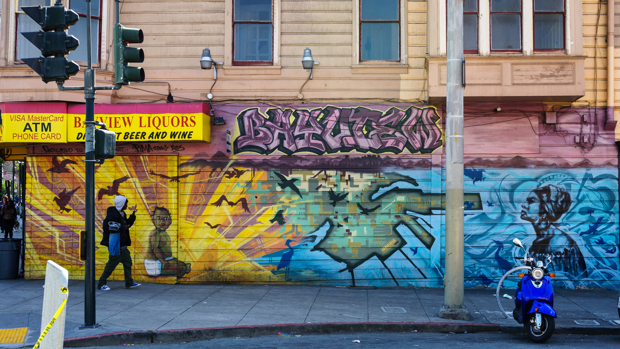 Black man in a hoodie carrying jeans walks past a mural outside a liquor store in San Francisco's Bayview neighborhood. Credit: Dale Cruse
