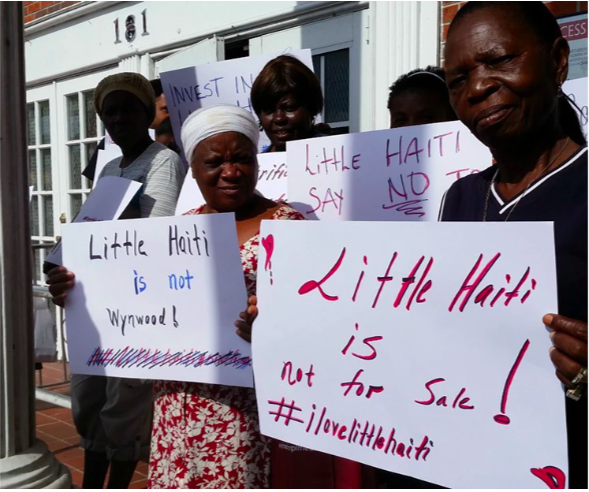"Women hold up signs that read ""Little Haiti is not for sale"""