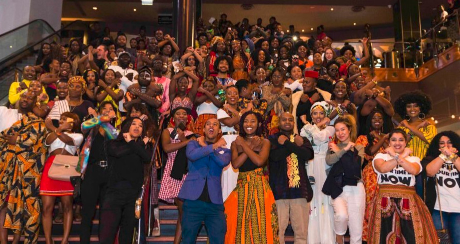 Photo by Emmanuel Mbala, The crowd at a Melbourne screen- ing of Black Panther, doing the Wakanda greeting. 2018