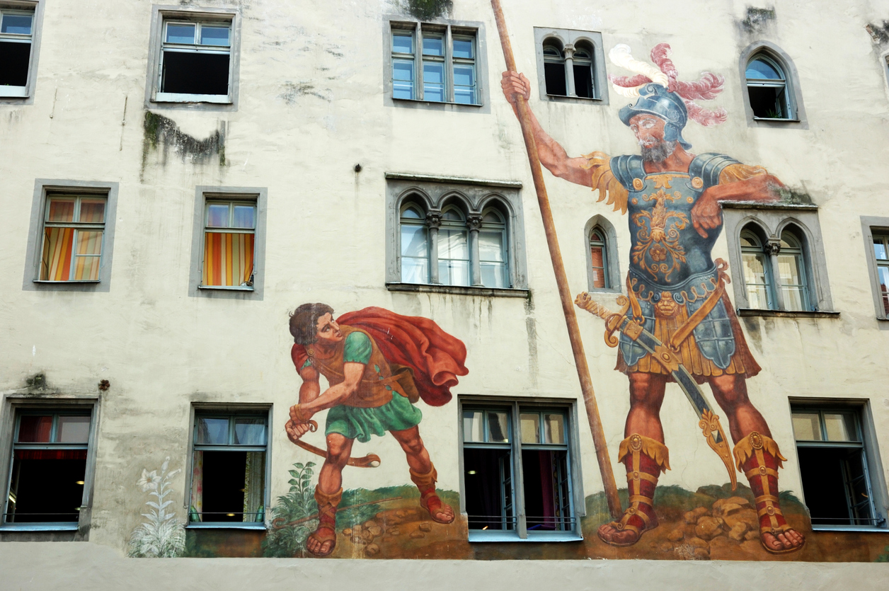 An image of a mural on the side of a building showing David and Goliath