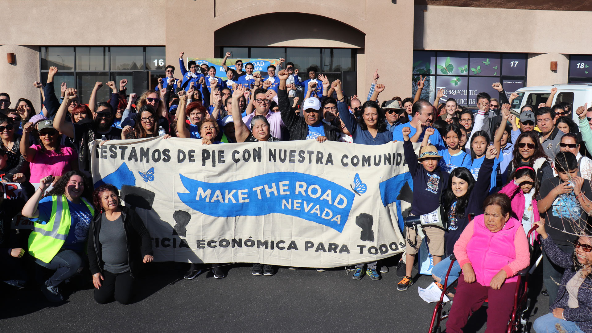 Make the Road Nevada staff members pose for a photo holding a banner in spanish