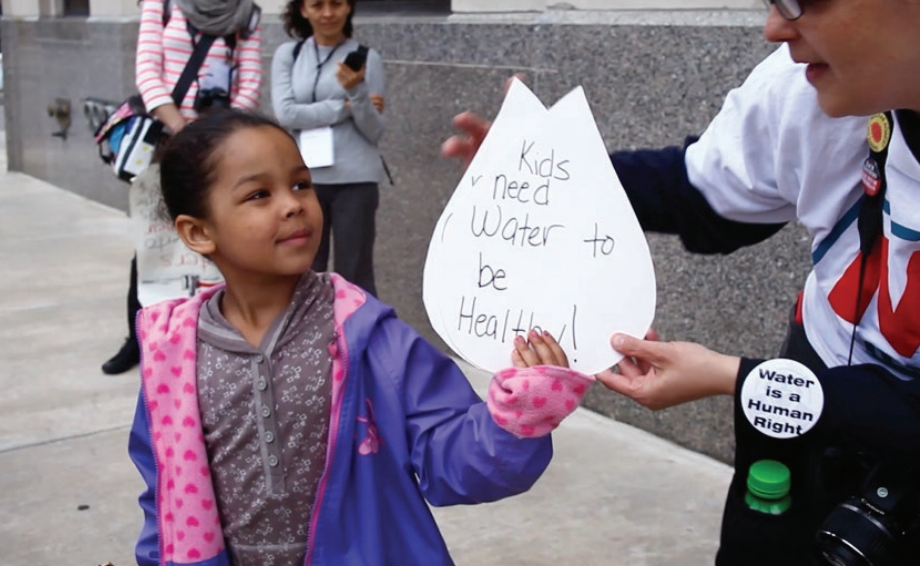 "This image shows a young girl holding a sign titles ""kids need water to be healthy!"" taken from the film I Do My Dying. Coutesy of Kate Levy, available online at detroitmindsdying.org."