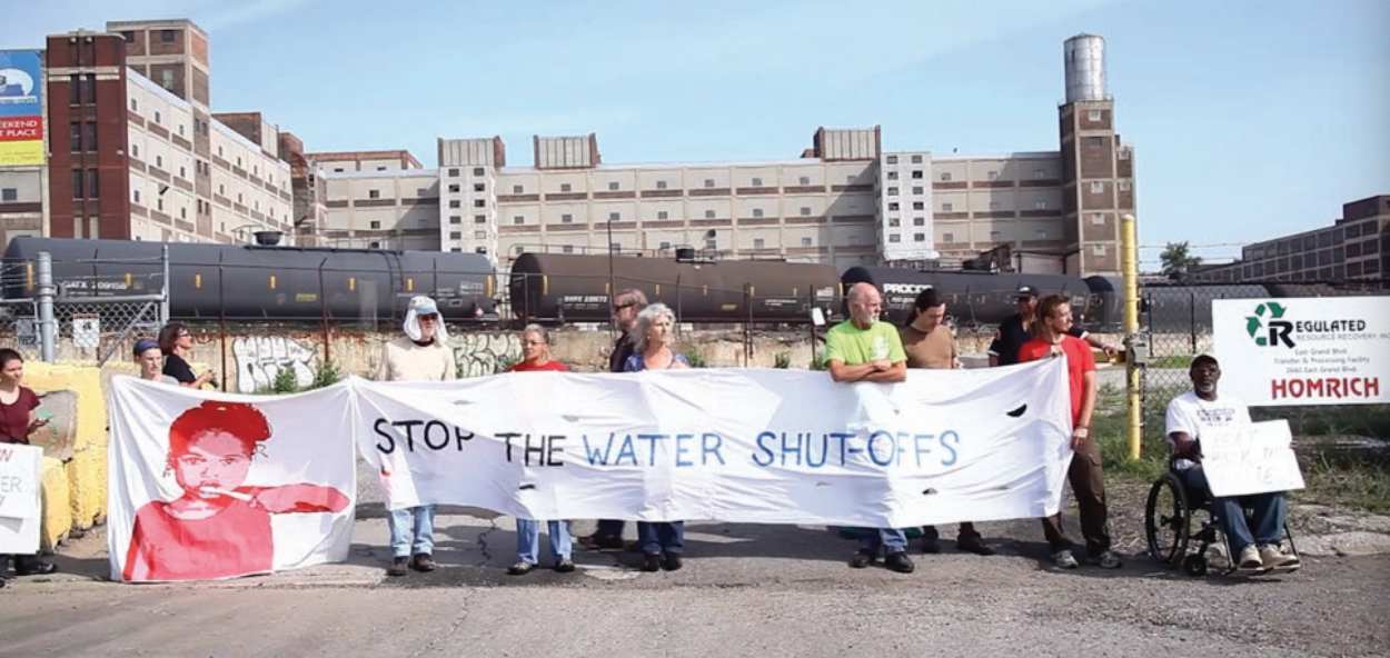 "This image, of citizens holding a sign saying ""Stop the water shutoffs"" is from the film I Do My Dying. Coutesy of Kate Levy, available online at detroitmindsdying.org."