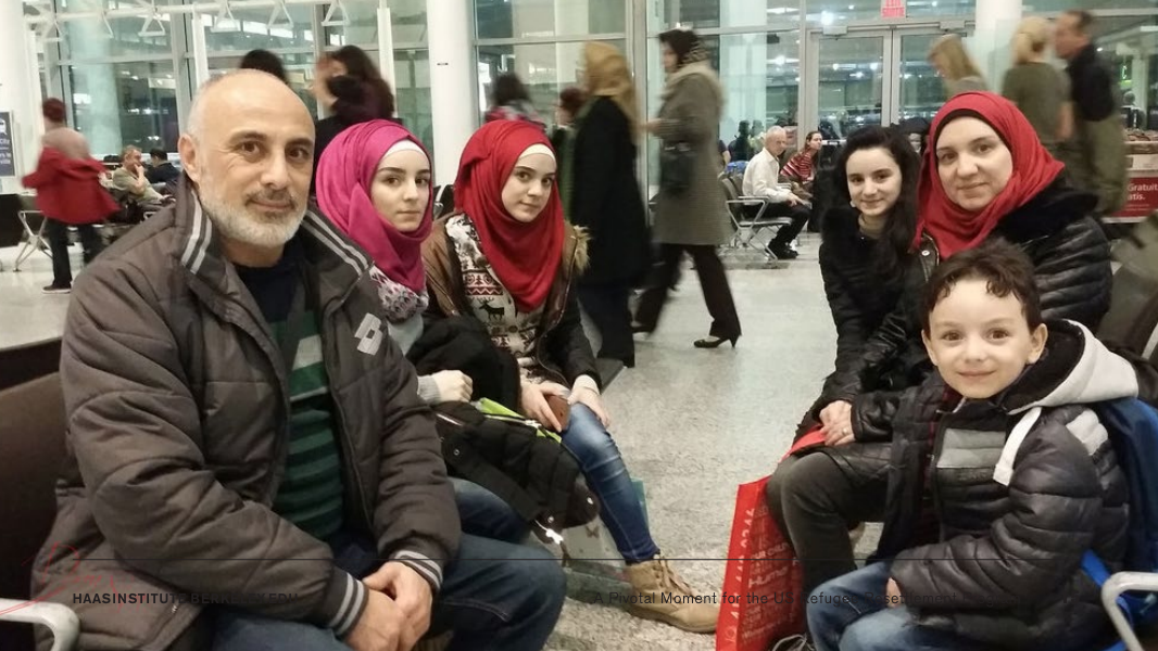This image includes 6 refugees sitting at the airport.
