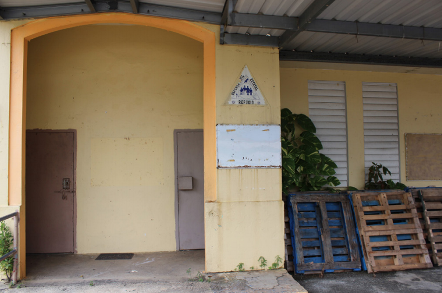 The entrance of the Luis Santaella school in Aguas Buenas features a triangular sign notifying citizens of the school's designation as a civil defense refuge.