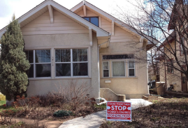 "This image is of a house with a sign on its yard reading ""STAND TOGETHER STOP FORECLOSURES STOP EVICTIONS"""