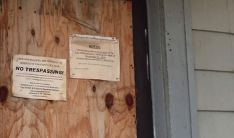 This image is of a house with 2 signs on the door - one notice from the city and one that says no trespassing