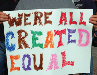 """This image is of a sign that reads """"We're all created equal"""""""