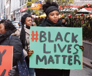 "This image is of a protestor holding a sign that reads ""#blacklivesmatter"""