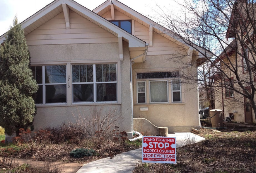 """This image is of a house with a sign on its yard reading """"stand together stop foreclosures stop evictions"""""""