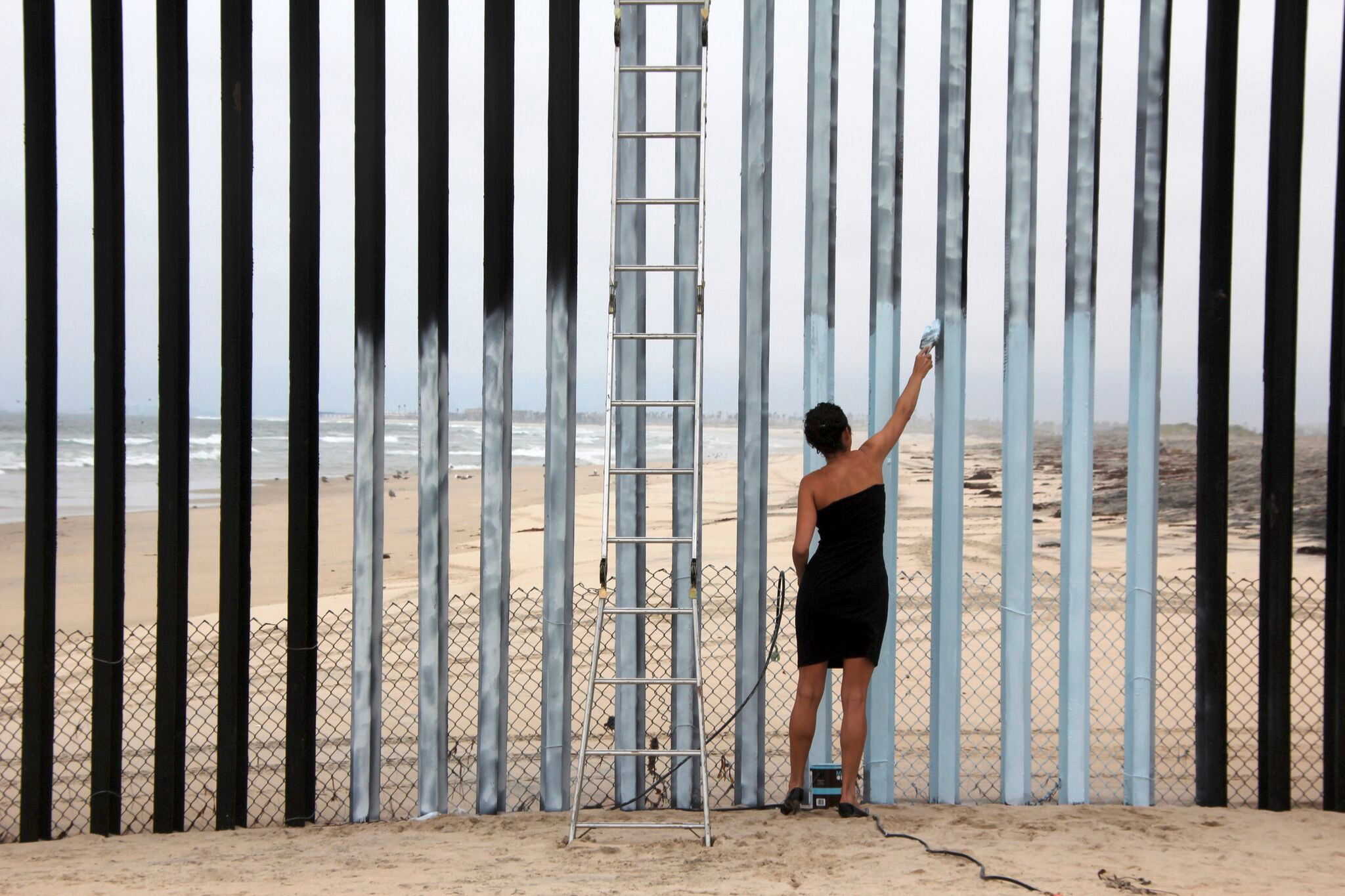 Borrando la Frontera (Erasing the Border), Ana Teresa Fernández. Performance at Tijuana/San Diego Border, 2011. Photographed by the artist's mother Maria Teresa Fernández, courtesy of artist and Gallery Wendi Norris